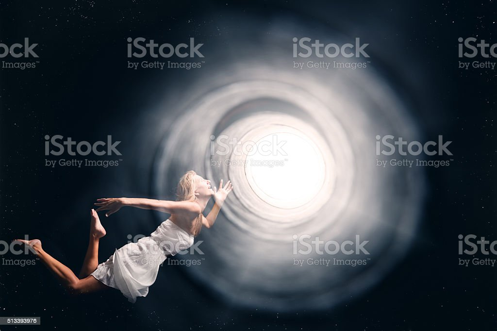Spirit Woman Floating Into A Tunnel Of Light stock photo