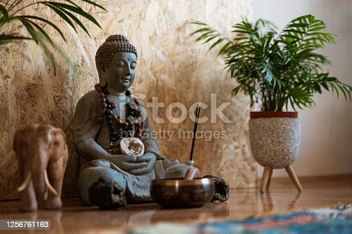 Statue of Buddha and a small meditation bell on the floor.