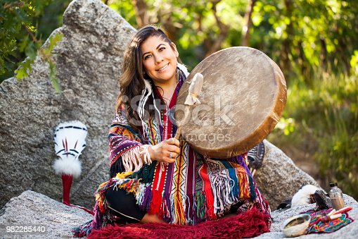 Spiritual ceremony with medicine woman. Latino woman wearing Peruvian style poncho, doing energy soul work.