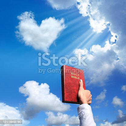 Female hand holding Holy Bible over shiny blue sky with heart shaped cloud