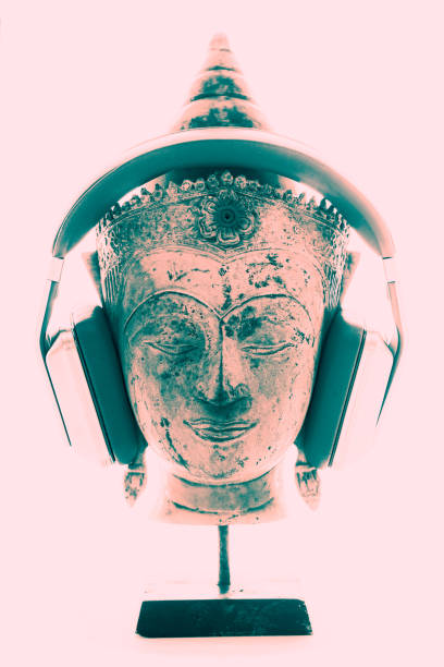 Spiritual music therapy. Bright contemporary image of Buddha head with headphones. Spiritual music therapy. Contemporary image of Buddha head with modern headphones representing religious, new age, chill-out or trance music. Divine pink white light background for purity, modernism and enlightenment. new age music stock pictures, royalty-free photos & images