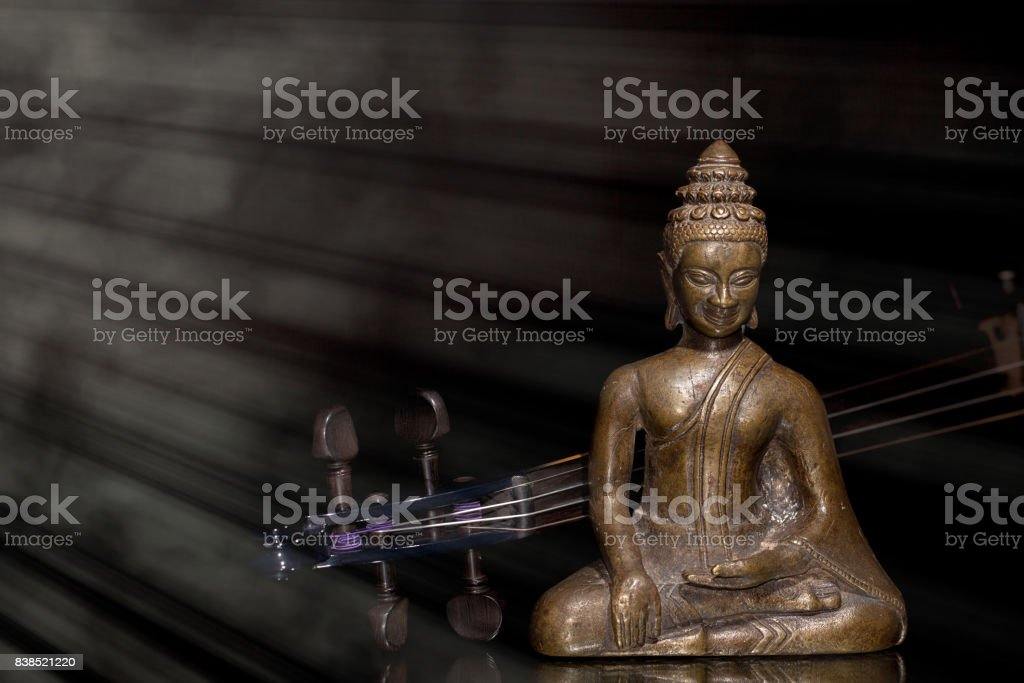 Spiritual, New Age, and religious music. Bronze buddha meditating with contemporary violin in divine beam of light. stock photo