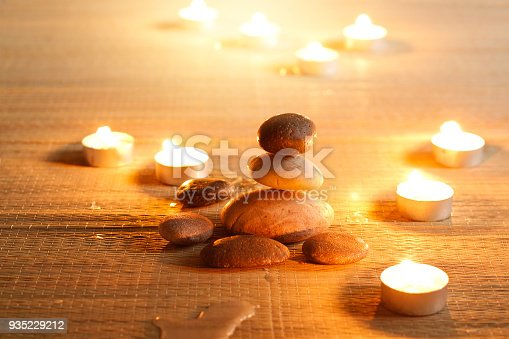 istock Spiritual purity atmosphere with oil lamps in temple. Stone balance on candle warm glowing background 935229212