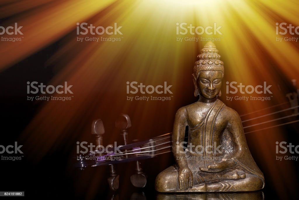 Spiritual, sacred or new age music. Buddha and violin under sun rays representing enlightenment. stock photo