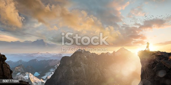 A single woman sitting in lotus meditation position on a rocky outcrop high above and looking out over a mountain range under a beautiful and awe inspiring sunset. The woman in half silhouetted against the setting sun as she meditates in stillness and tranquility in nature as part of her spiritual journey.