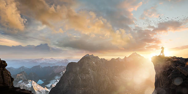 spiritual seeker meditating high on mountain top at sunset - aura stock photos and pictures