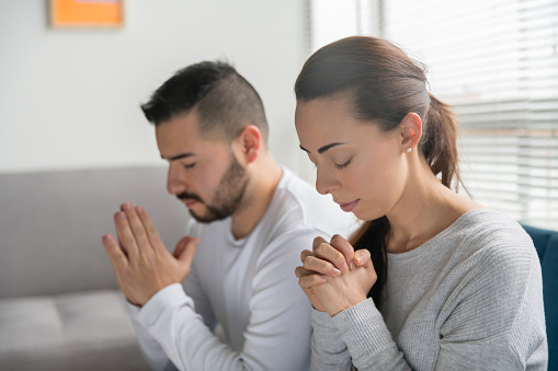 Portrait of a spiritual young Latin American couple praying together at home - religion concepts
