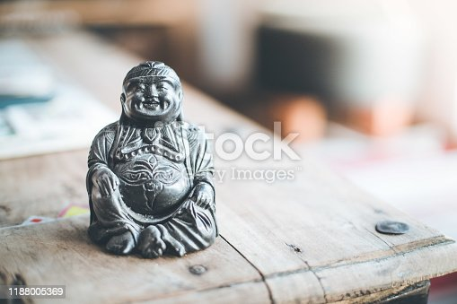 Feng shui: Buddha statue at on a table in the own living room.