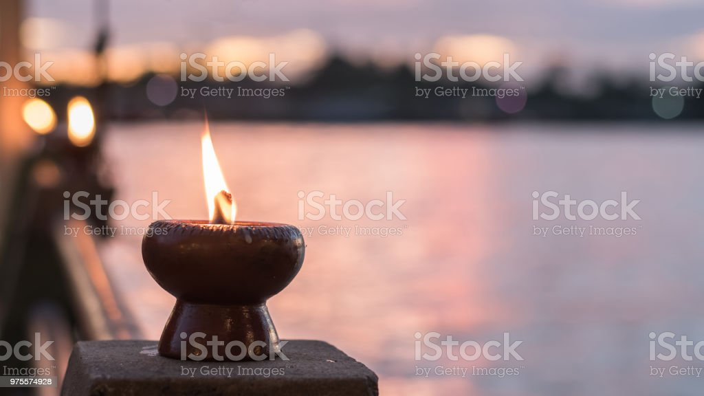 Spirituality and tranquility abstract concept with candle light illumination and golden sunset sky stock photo