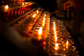 Spirituality.  One man lighting a red candle in a Catholic church chapel in New York City, USA.  The glowing candles are lined up in a row. Diminishing perspective.  The candles serve as a vigil or spiritual prayer.  Reverence, hope, religion.