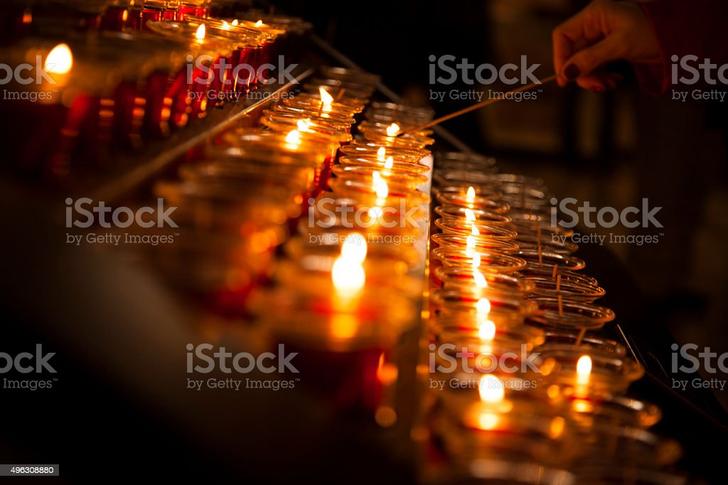 Spirituality.  Lighting red candles in Catholic church. stock photo