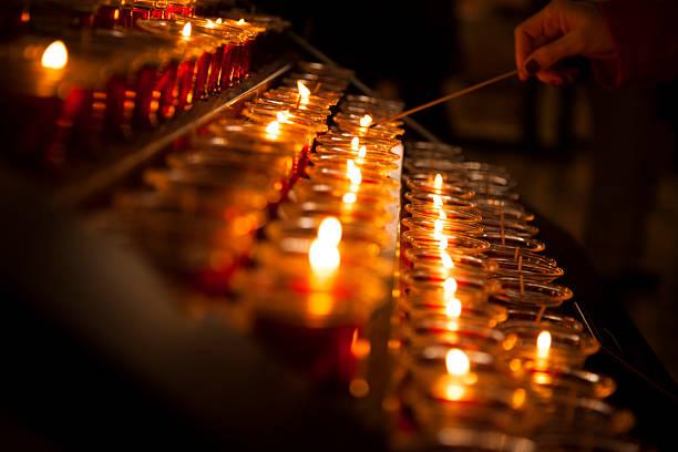 spirituality.  lighting red candles in catholic church. - hand tänder ett ljus bildbanksfoton och bilder