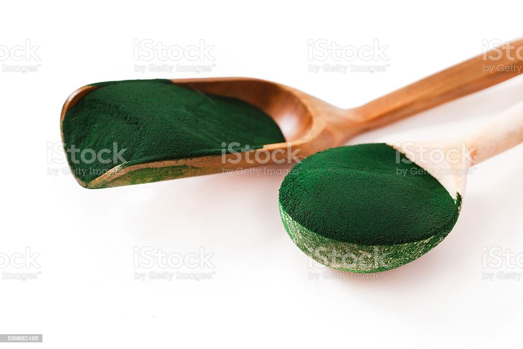 Spirulina algae powder in the wooden scoops stock photo