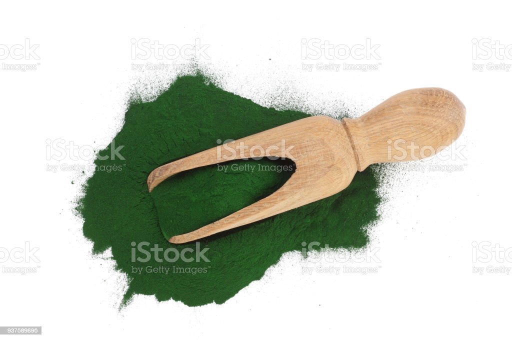 Spirulina algae powder in wooden scoop isolated on white background. Top view stock photo