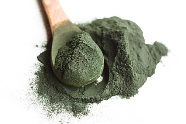 alga espirulina polvo en una cuchara de madera - algas fondo blanco fotografías e imágenes de stock