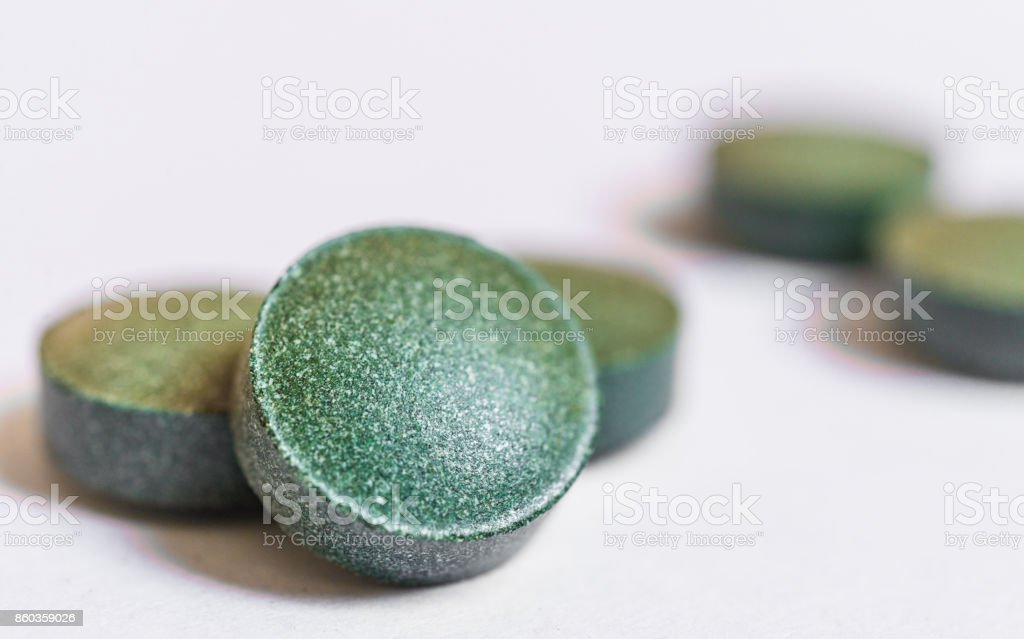 Spirulina pills tablets macro photo against white background. Dietary supplement, superfood, fitness, and healthy eating concept. stock photo