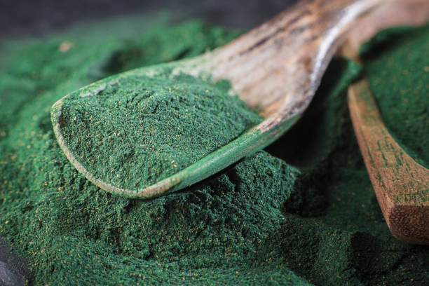 spirulina pulver och tabletter på trä bakgrund - spirulinabakterie bildbanksfoton och bilder