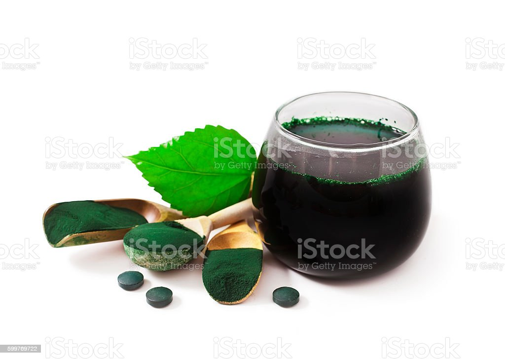 Spirulina powder in the wooden scoops and cup of drink stock photo