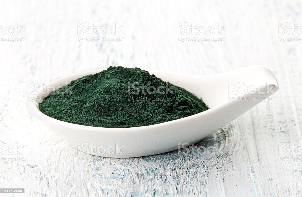 Spirulina powder in white porcelain spoon stock photo