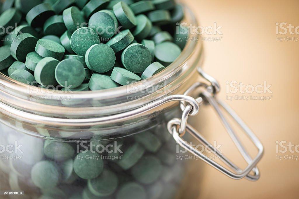 Spirulina supplement pills into airtight jar. Antioxidant alga nutrition. stock photo