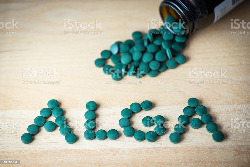 Spirulina supplement pills making up the word alga stock photo