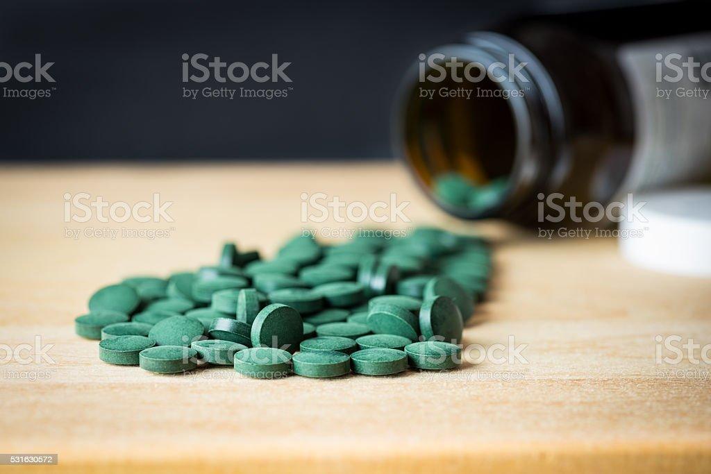 Spirulina supplement pills spread on wooden board stock photo