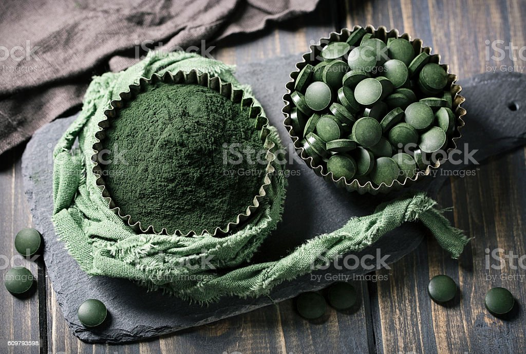 Spirulina tablets and powder in bowls stock photo