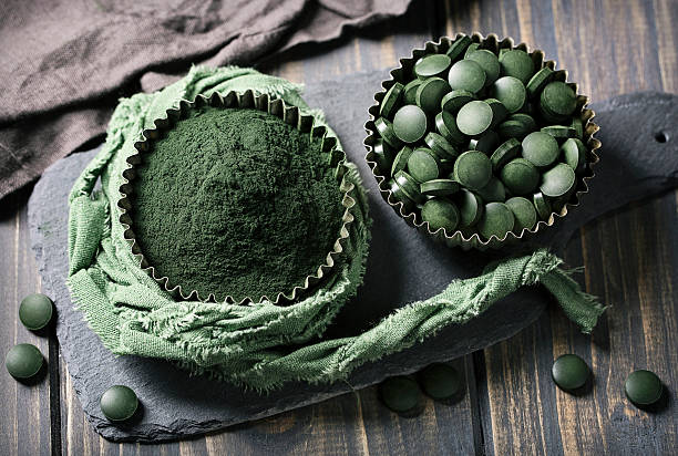 Spirulina tablets and powder in bowls – Foto