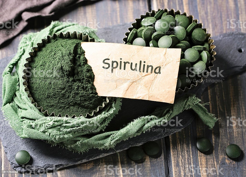 Spirulina tablets in a bowl stock photo