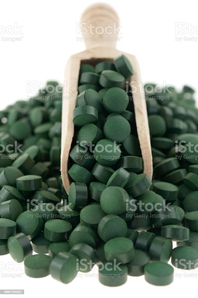 spirulina.Algae spirulina tablets in a wooden scoop isolated on a white background. organic Super food - Royalty-free Alemanha Foto de stock
