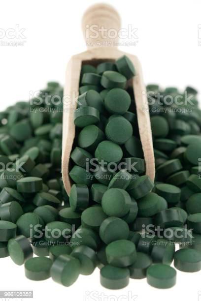 Spirulina Alger Spirulina Tabletter I En Trä Skopa Isolerad På En Vit Bakgrund Organiska Super Mat-foton och fler bilder på Alger - Växt