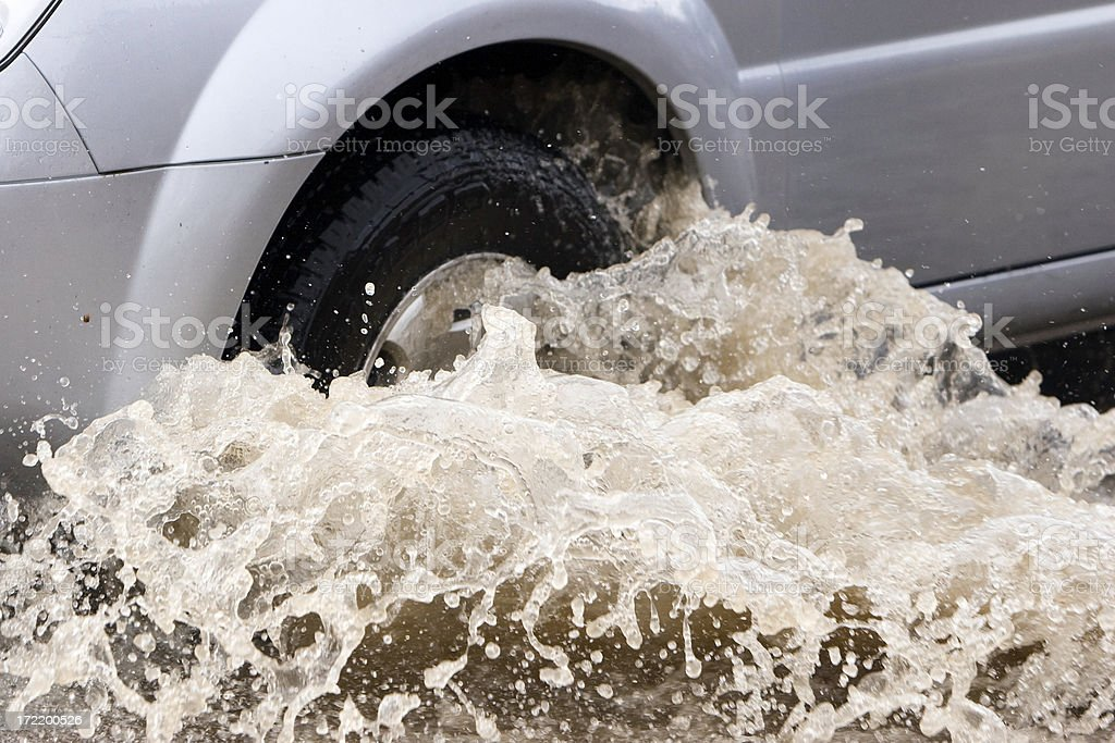 Splash by a car as it goes through flood water royalty-free stock photo