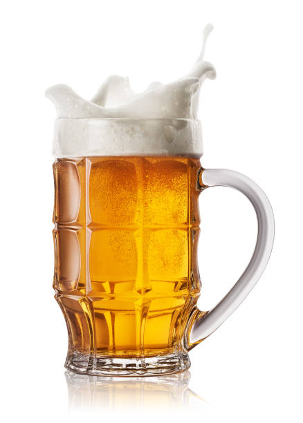 Splash in beer mug Splash in beer mug isolated on white background. Splash foam in faceted mug of light beer lager stock pictures, royalty-free photos & images