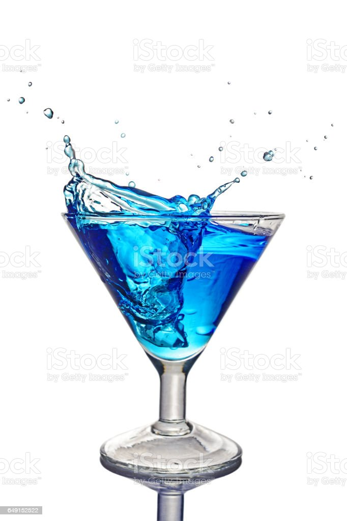 Splash in glass of a blue alcoholic cocktail stock photo