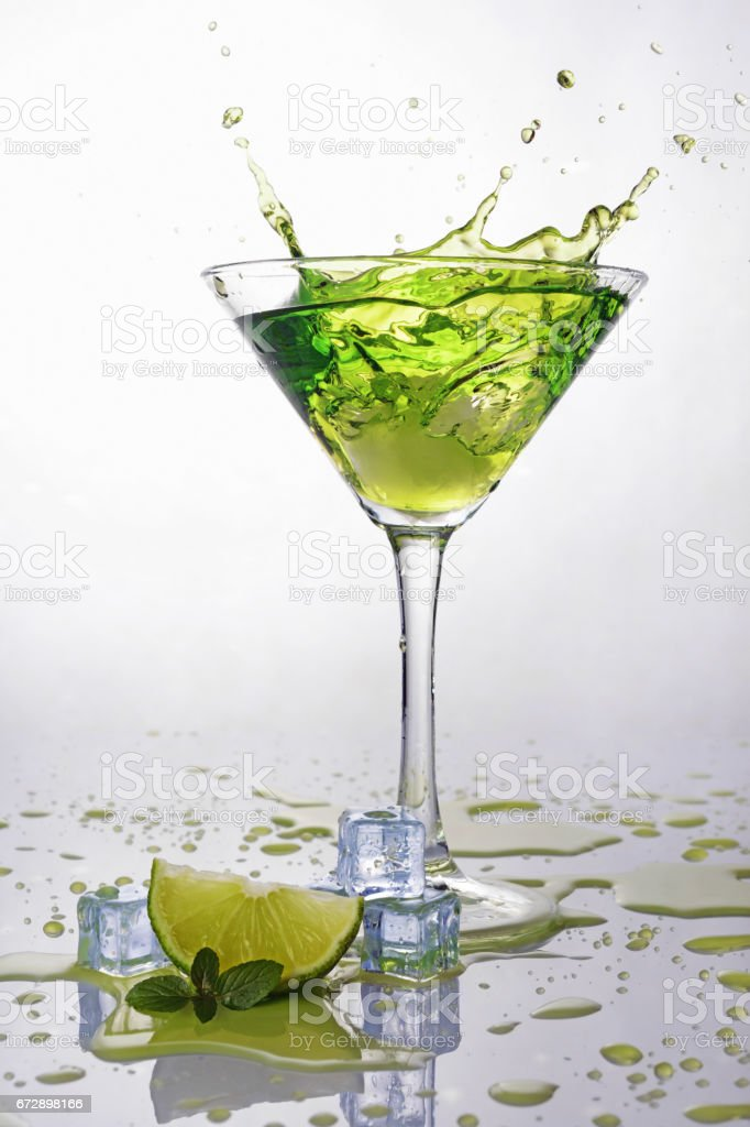 Splash in glass of green alcoholic cocktail drink with lime, mint and ice cube stock photo