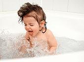 Cute little girl splashing water in the bathtub