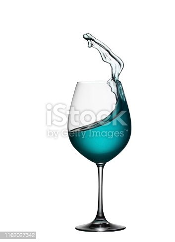 Splash of blue drink in glass on white isolated background. The splashing of blue water is like a sea wave in a glass. A splash of blue cocktail in a wine glass closeup.