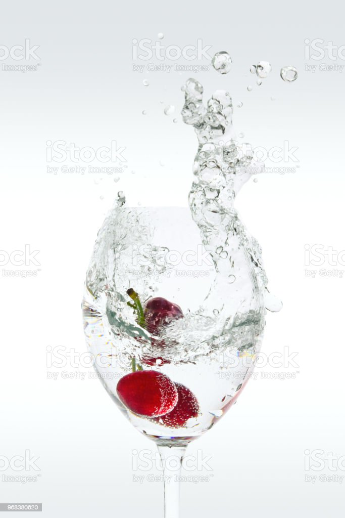 Splash of carbonated water in a glass with cherries stock photo