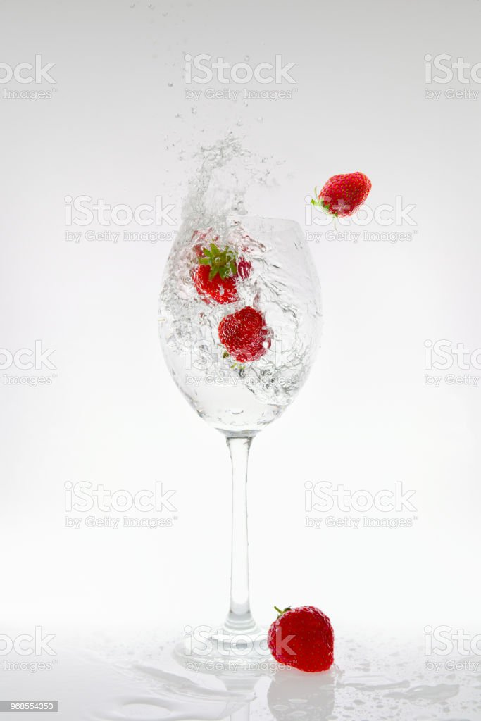 Splash of carbonated water in a glass with strawberries stock photo