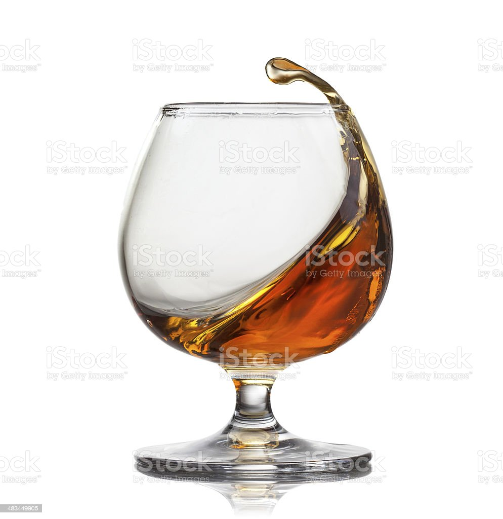 Splash of cognac in glass isolated on white background stock photo