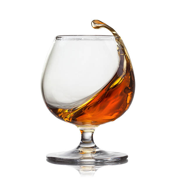 Splash of cognac in glass isolated on white background Splash of whiskey with ice in glass isolated on white background brandy stock pictures, royalty-free photos & images