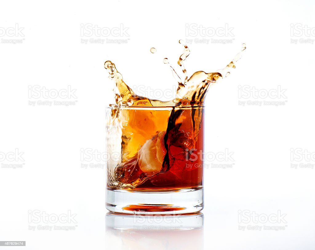 splash of cola in glass isolated on white background stock photo