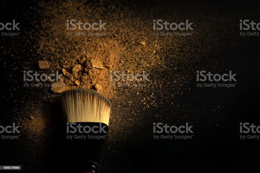 Splash of golden beige cosmetic powder and brush on black background and soft light. stock photo