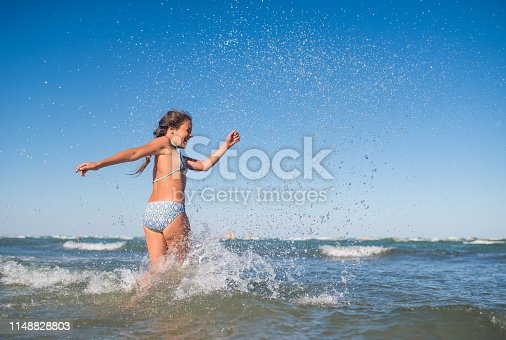 The girl splashes standing in the sea.