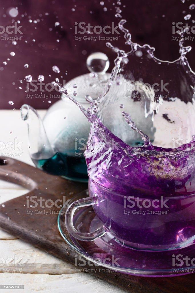 Splash of violet Butterfly Pea tea in a glass cup, Clitoria Ternatea tea, selective focus stock photo