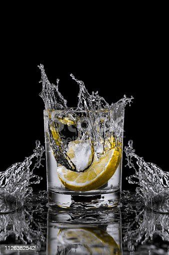 A splash of water in a transparent glass of ice and lemon on a black background.
