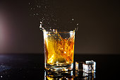 Splash of whiskey with ice cubes in glass on black background