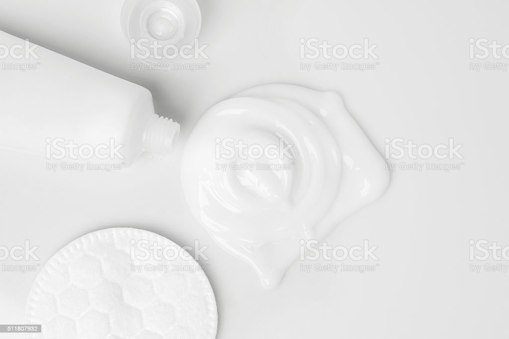 splash of white cream, tube and cosmetic cotton disk stock photo