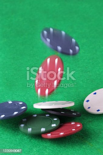 Splash the pot. Casino chips falling onto a card table with partial blur to illustrate movement