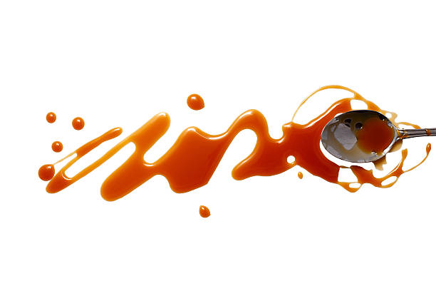 splashes and spilled caramel with a spoon - karamel stockfoto's en -beelden